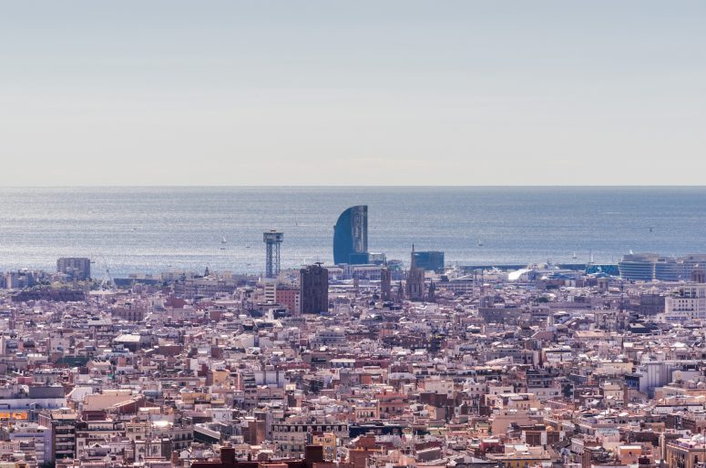 Panoramic view of Barcelona city from highest hill. Daysun lights out all the city, quarters, Mediterranean Sea and endless sky.