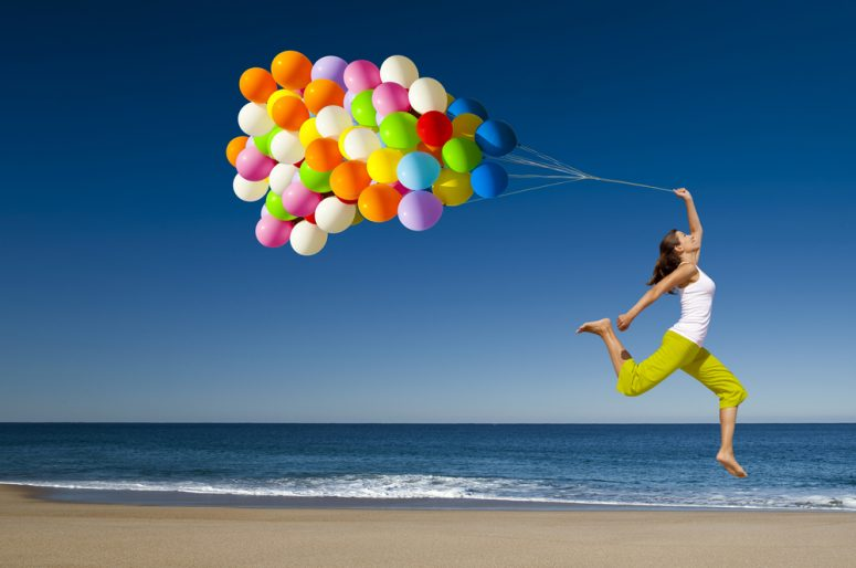 Beautiful and athletic girl with colorful balloons jumping on the beach