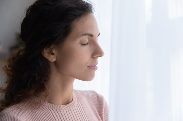 Calm young woman stand meditate with eyes closed