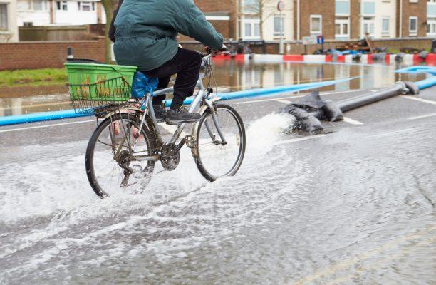 Cyclist On Flooded Urban Road