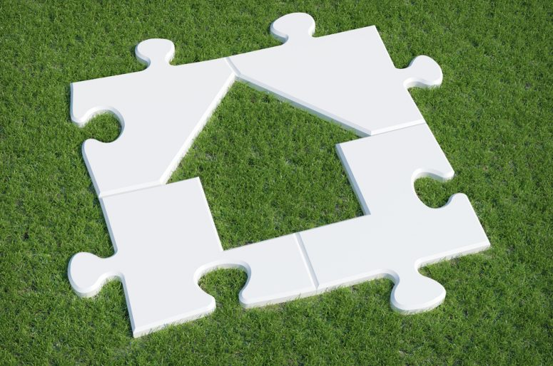 Puzzle house symbol on grass